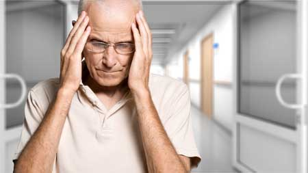 elderly man holds his head