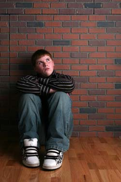 teenage boy sitting on floor with arms on knees