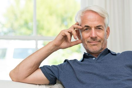Retired mature man sitting on couch and looking at camera.